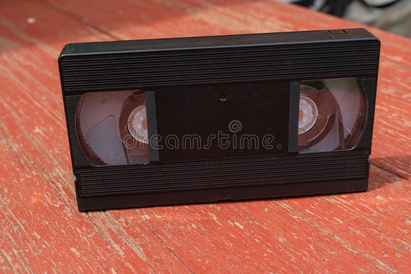 Old black VHS video tipe cassette on the red wooden floor. Old black VHS video tipe cassette on the red wooden table royalty free stock photo
