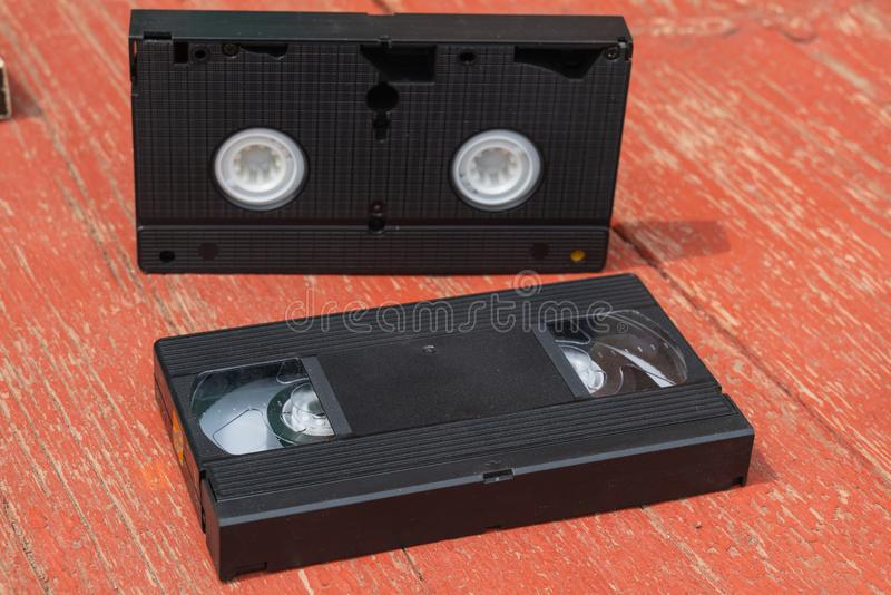 Old black VHS video tipe cassette on the red wooden floor. Old black VHS video tipe cassette on the red wooden table stock photo