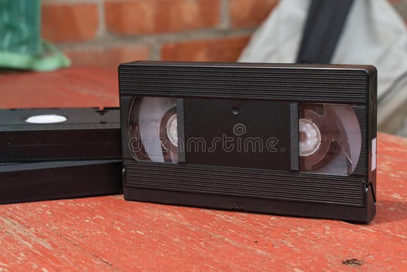 Old black VHS video tipe cassette on the red wooden floor. Old black VHS video tipe cassette on the red wooden table royalty free stock photography