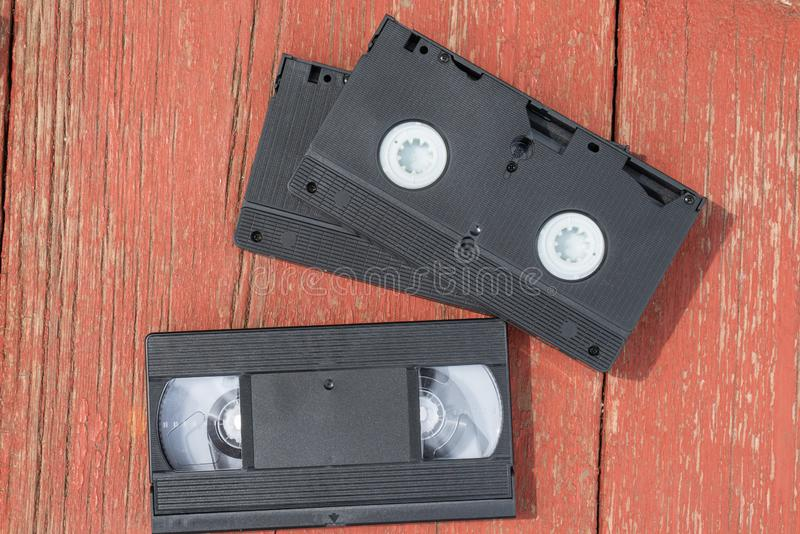 Old black VHS video tipe cassette on the red wooden floor. Old black VHS video tipe cassette on the red wooden table stock image