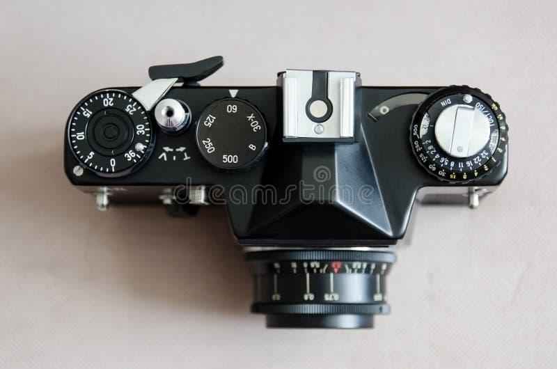 Old black vintage camera. On brown background stock images