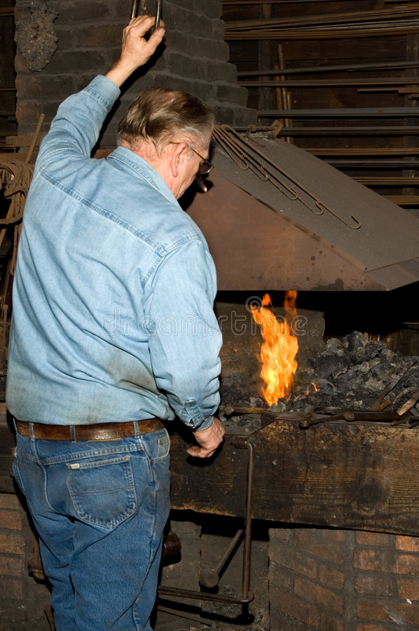 Old Blacksmith at the Forge stock image