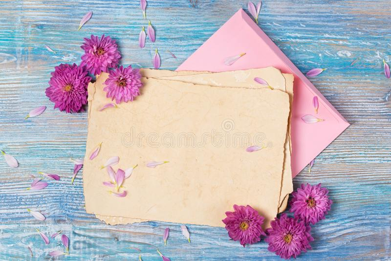 Old blank paper, envelope and pink flowers on blue wooden background royalty free stock image