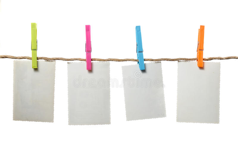 Old Blank Photos Hanging on Rope. Four old blank photos hanging on a rope against a white background royalty free stock images