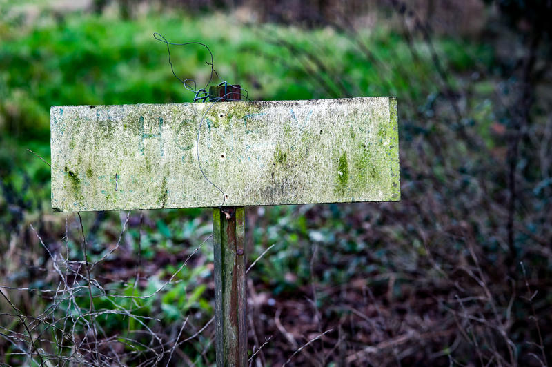 Old blank sign. Old, disused blank sign on grass verge in a semi rural setting stock photography