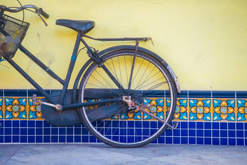 Old Blue bicycle on the old street. Parked next to the yellow and blue wall stock photography