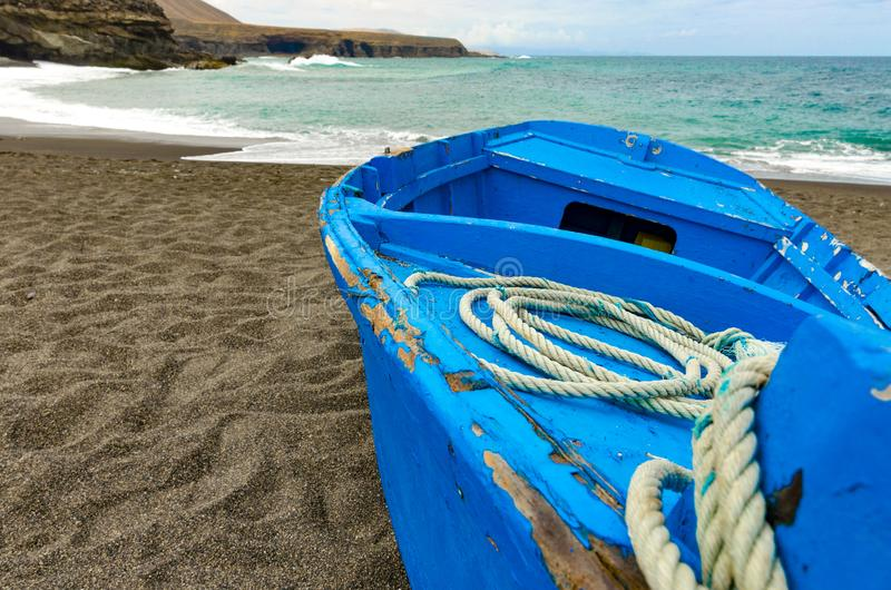 A blue boat on a black beach. An old blue boat with a coil of rope on the black volcanic beach with rocks and calm ocean bay in the background royalty free stock photography