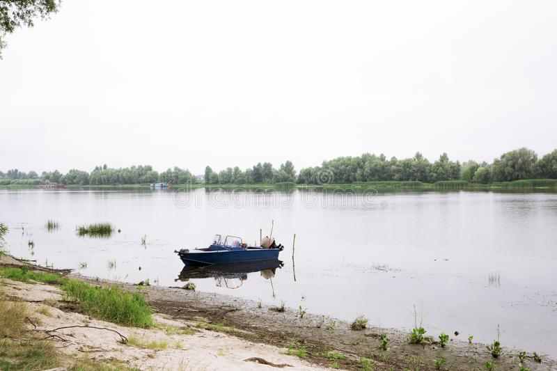 Old blue boat on the river bank. picturesque water landscape. calm and relaxing summer day. Old blue boat on the river bank. picturesque summer water landscape stock photo