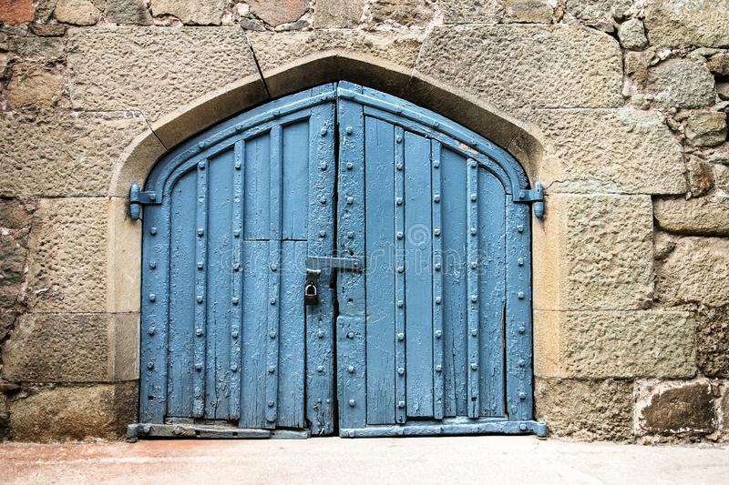 Old blue door or gate in stone wall, locked royalty free stock photo