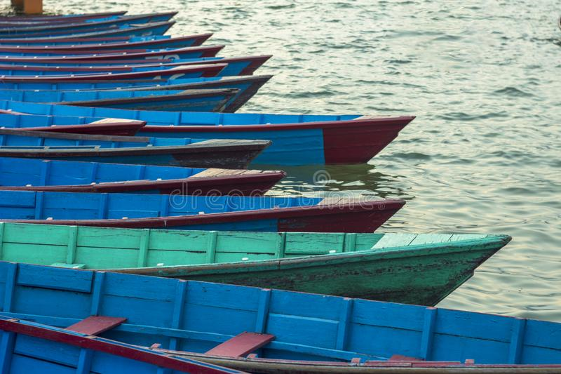Old blue empty wooden boats on the water at the pier in a row against the blurred background of boats royalty free stock images