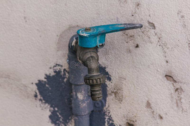 Old blue faucet is on a white wall. stock image