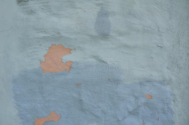 Old blue flaking paint on wall with orange underneath royalty free stock photo