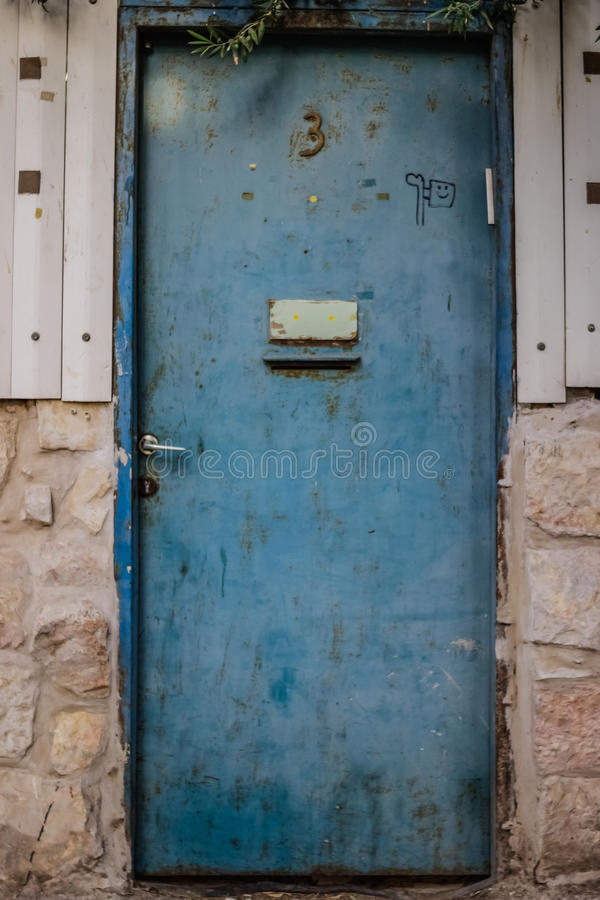 Old blue metal dirt door with mailbox and rusty metal lockas a beautiful vintage background. Old blue metal dirt door with mailbox and rusty with openwork a royalty free stock photos