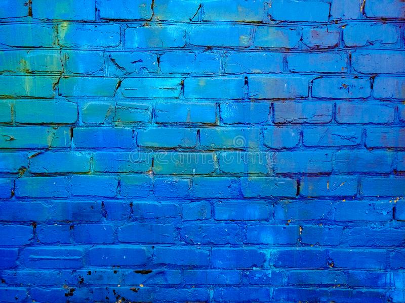 Close up image of painted brick wall surface. An old blue painted brick wall with peeling paint for textures, backgrounds and designe royalty free stock photos