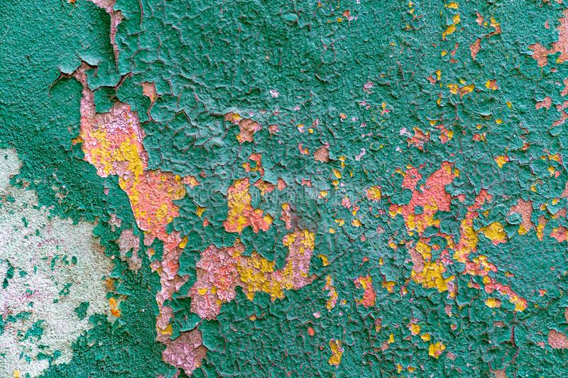 An old blue painted wall with pealing paint, pink and orange spots stock photo