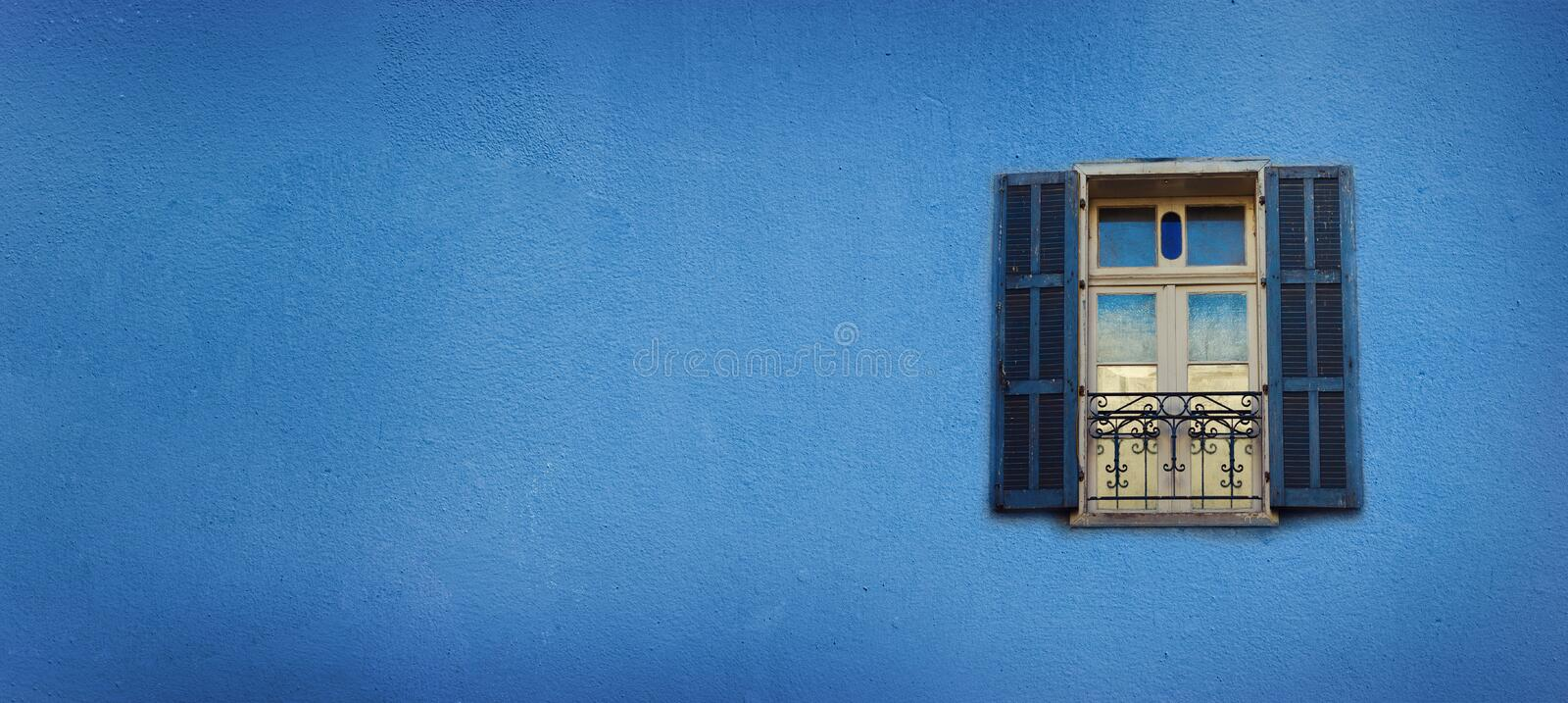 Old blue painted windows on concrete wall. Banner with copy space. Pop art concept, greek style window stock photography