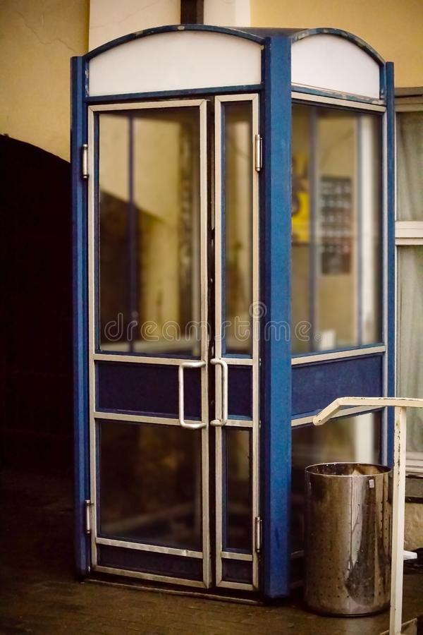 Old blue phone booth in a corner of yellow building royalty free stock photo