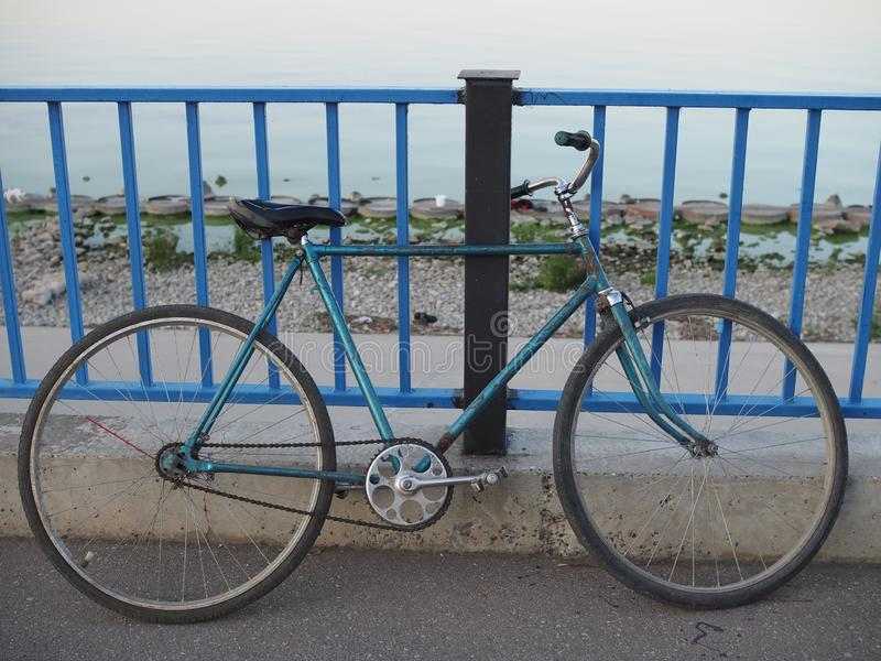 Old blue retro bike with rust places chained lock to the bars on the waterfront stock photos