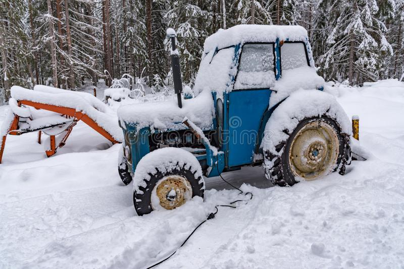 Old blue tractor standing covered in snow. Old blue tractor standing in snow in sweden february 2019 royalty free stock images