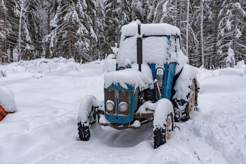 Old blue tractor standing covered in snow. Old blue tractor standing in snow in sweden february 2019 royalty free stock image