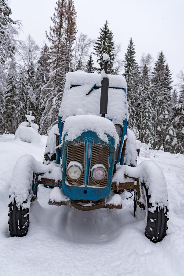 Old blue tractor standing covered in snow. Old blue tractor standing in snow in sweden february 2019 stock photos