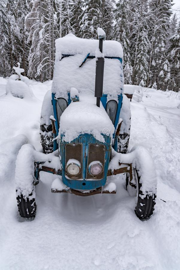 Old blue tractor standing covered in snow. Old blue tractor standing in snow in sweden february 2019 stock image