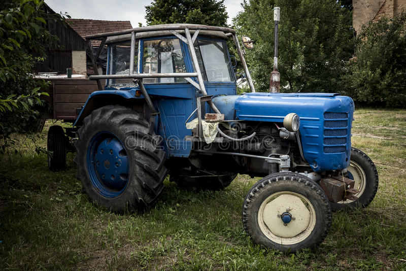 Old blue tractor standing in the garden. In front of the house royalty free stock photography