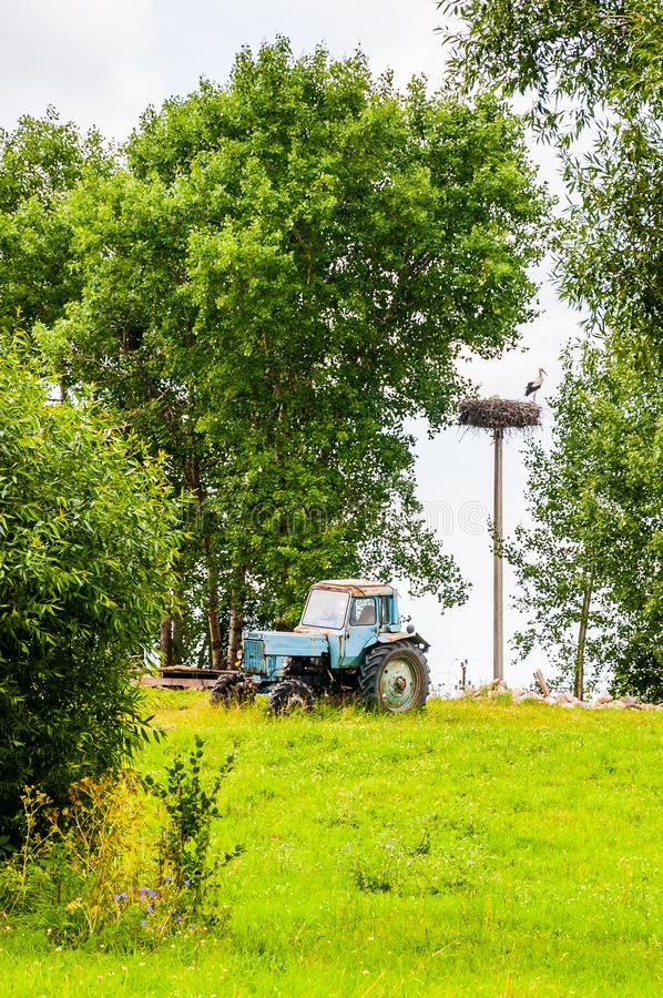 Old blue tractor standing on a meadow with column on which stork made a nest surrounded by green summer flora. Old blue tractor standing on a meadow with column stock photo