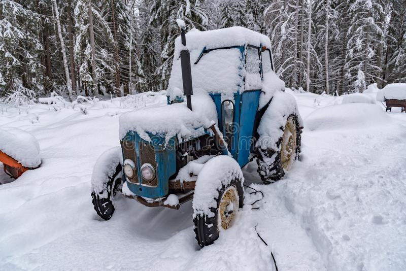 Old blue tractor standing covered in snow. Old blue tractor standing in snow in sweden february 2019 royalty free stock photography