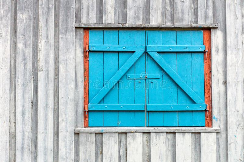 Old and blue window/barn doors on rustic grey and weathered wooden wall stock photos