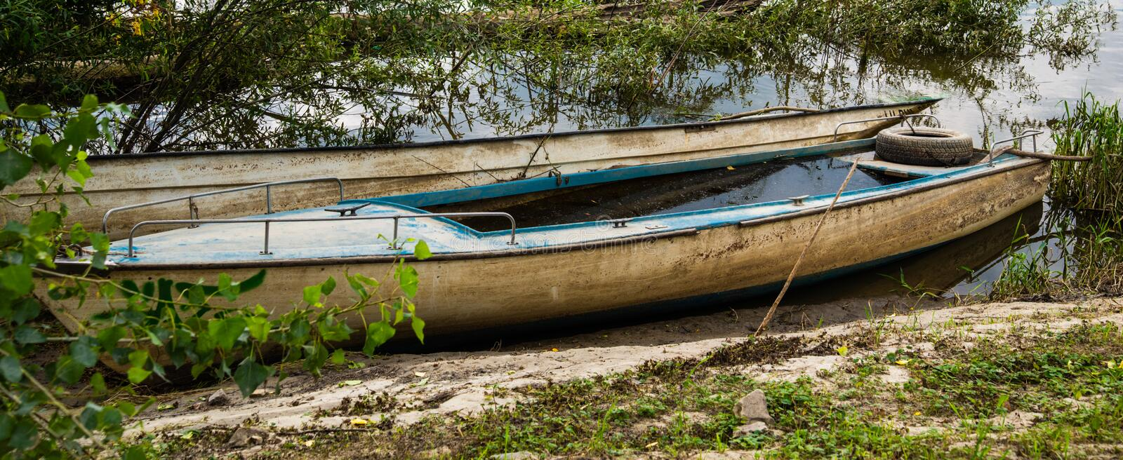 Old blue wooden abandoned fishing boat sunk on the shore of a river. Boat full of water royalty free stock images