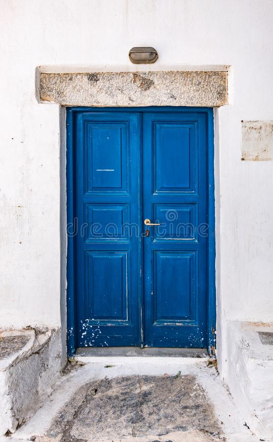 Blue double painted door in Greece. Old blue wooden door of traditional white house in Amorgos, Greece. Vertical image royalty free stock photo