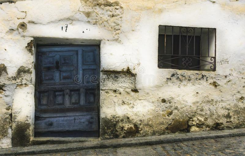 Old blue wooden door and wrought iron window on white lime wall. Pedro Bernardo, Avila, Spain stock photo