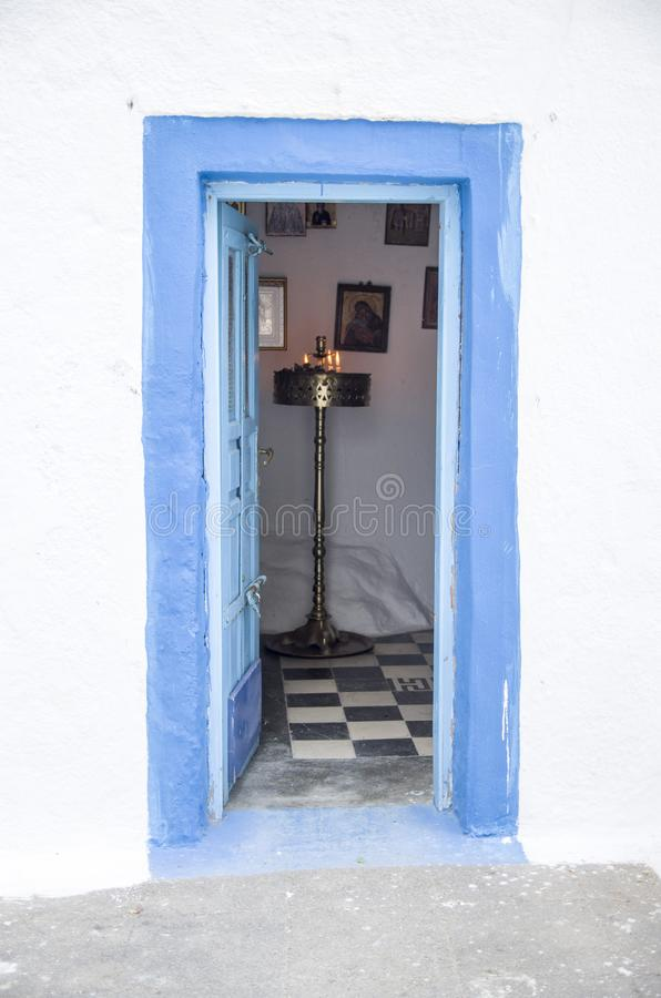 Old blue wooden open church door on white wall, santorini. Old blue wooden open church door on white wall, Greece stock image