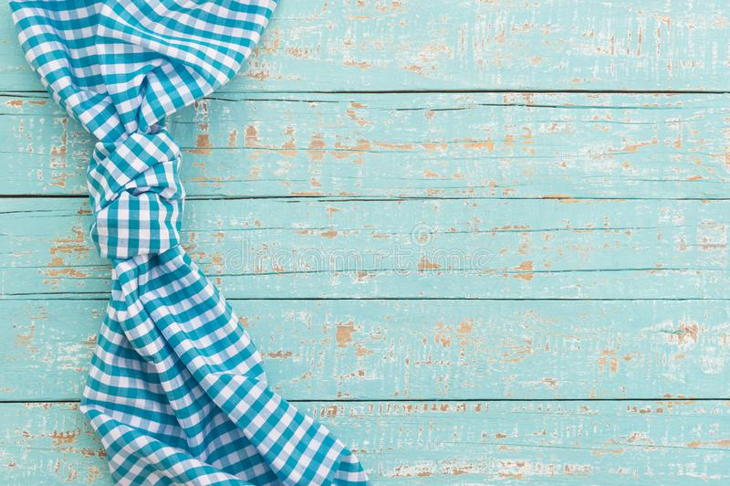Old blue wooden table surface with rustic checked tablecloth stock photo