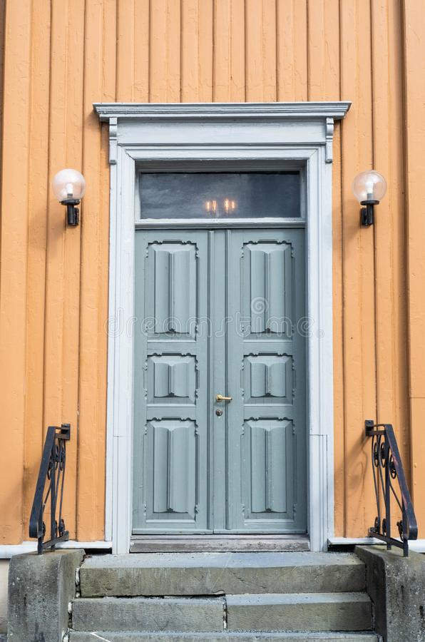 Old blue wooden vintage door with stone porch, railing and lamps on the yellow facade stock photo