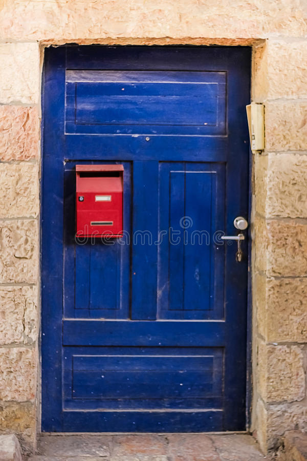 Old blue woodl dirt door with red mailbox and rusty metal lockas a beautiful vintage background stock photos