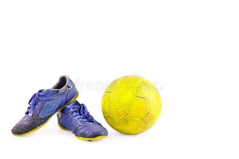 Old blue worn out futsal sports shoes and yellow futsal ball on white background football object isolated royalty free stock photography