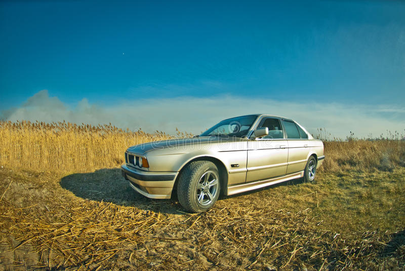Old BMW of 5 series. Golg old BMW of 5 series costs in the field, e34, 525 royalty free stock photography