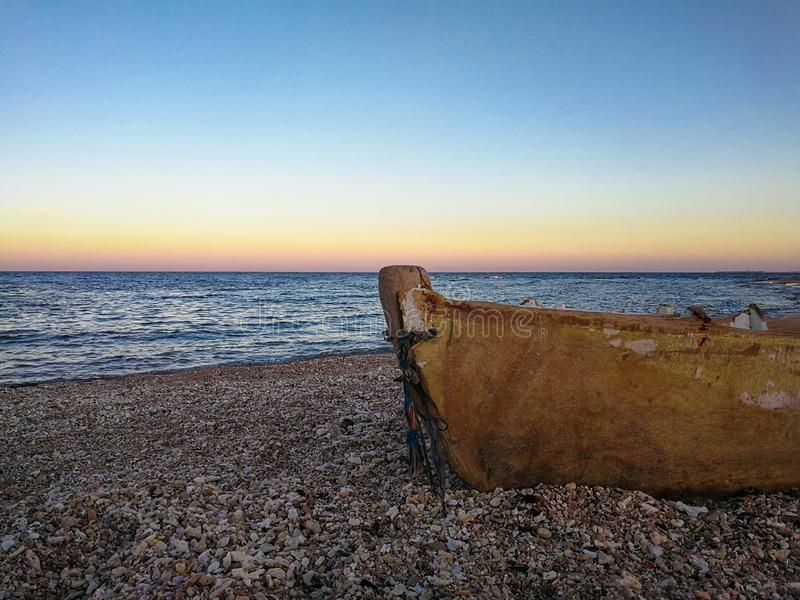 Old boat on the beach at sunset stock photography