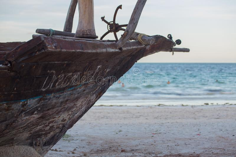 An old boat on the coastline on background of horizon line. 2018.02.21, Kiwengwa, Tanzania. An old boat on the coastline on background of horizon line. Travel royalty free stock image