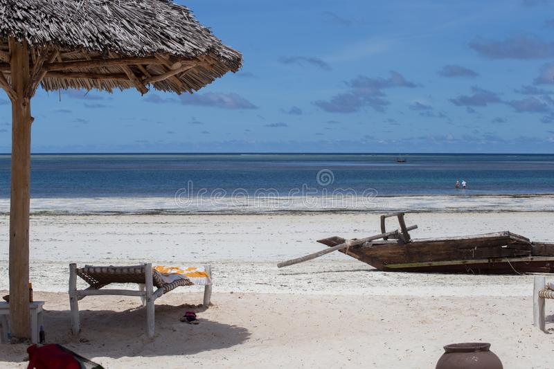 An old boat on the coastline on background of horizon line. 2018.02.21, Kiwengwa, Tanzania. An old boat on the coastline on background of horizon line. Travel royalty free stock photography