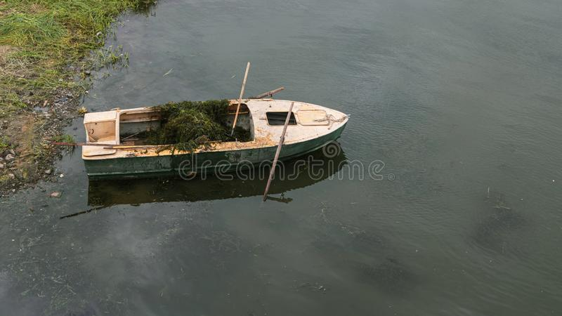 Old boat in the lake near the shore. Water purification of the river from algae.  stock image