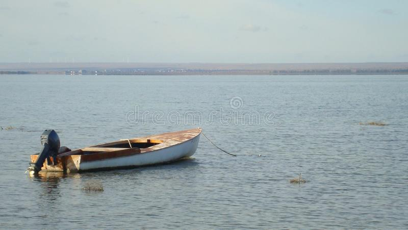 Old boat with motor on the calm water of the wide sea Bay in a warm evening royalty free stock images