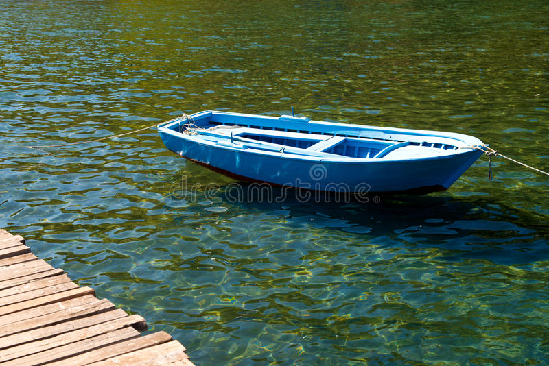 An old boat near a wooden bridge on a beautiful lake. Fishing boat on the pier. royalty free stock image