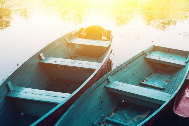 Old boat with oar near river or beautiful lake. Calm sunset on the nature. Fishing boat. Reflections in water, romantic lagoon landscape royalty free stock photo