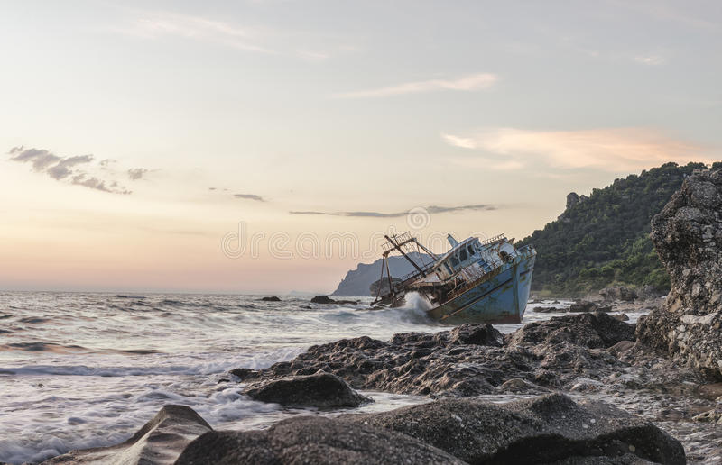 Old boat on the sea beach. Sunset on the Greek coast stock image