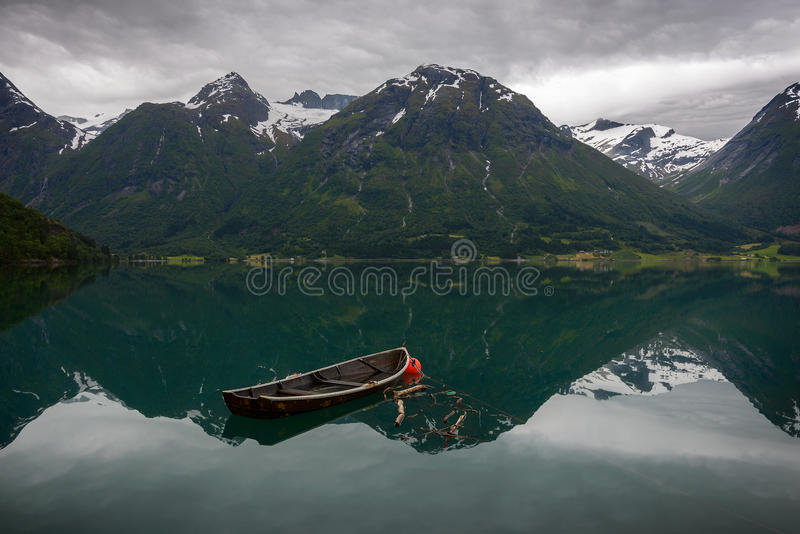 An old boat and reflection of the mountains in the water royalty free stock image