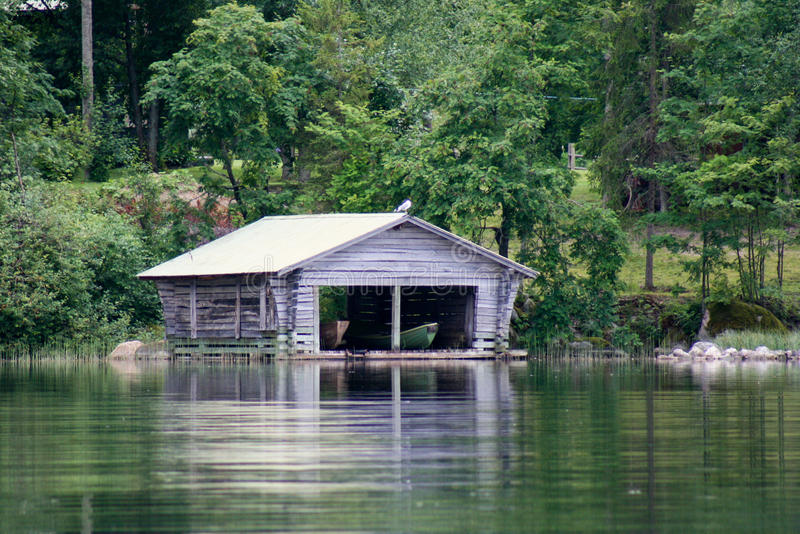 Old Boathouse by the Lake. Old Boathouse with two boats by the Lake stock photo