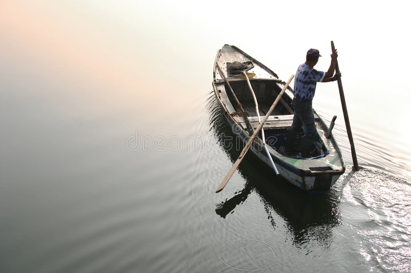 The old boatman. A boatman on a calm lagoon against the sun light reflected on water royalty free stock photos